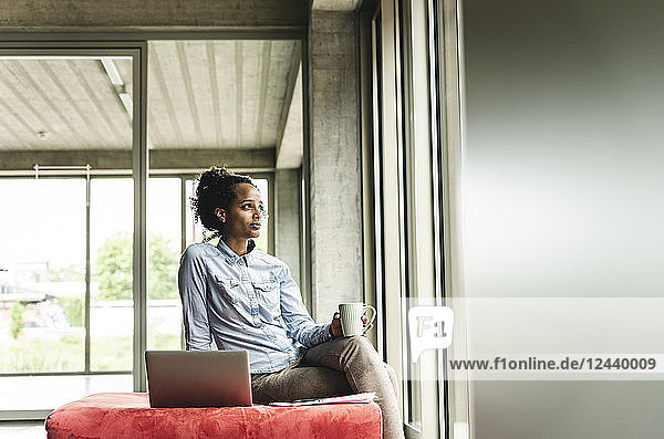 young businesswoman working in modern office  sitting on stool  using laptop