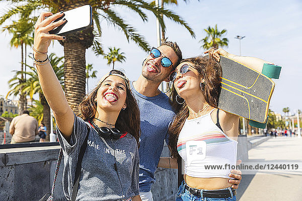 Three playful friends with skateboard taking a selfie