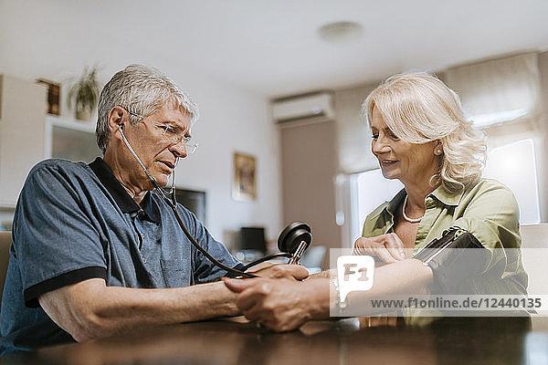 Senior couple taking blood pressure