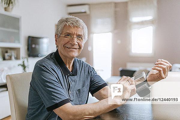 Smiling senior man taking his blood pressure