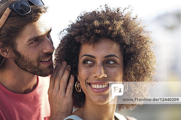 Happy young couple  man whispering into woman's ear