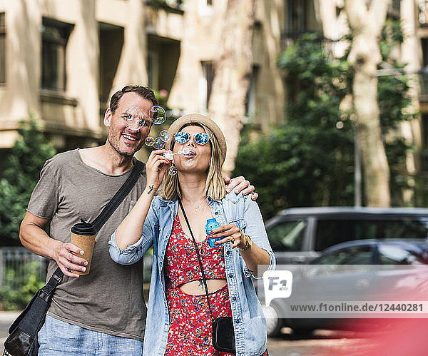 Happy couple with coffee to go blowing soap bubbles in the city