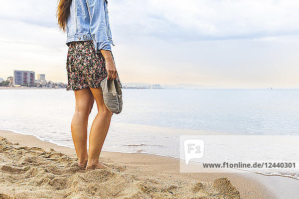 Spain  Barcelona  woman standing barefoot on the beach
