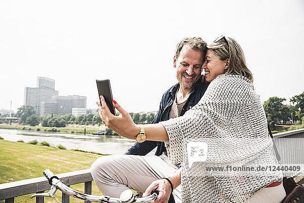 Happy couple taking a selfie on a bridge