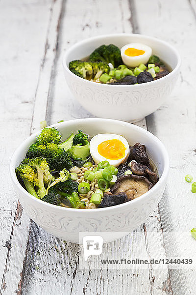 Two bowls of Ramen soup with egg  broccoli  noodles  shitake mushroom and spring onions