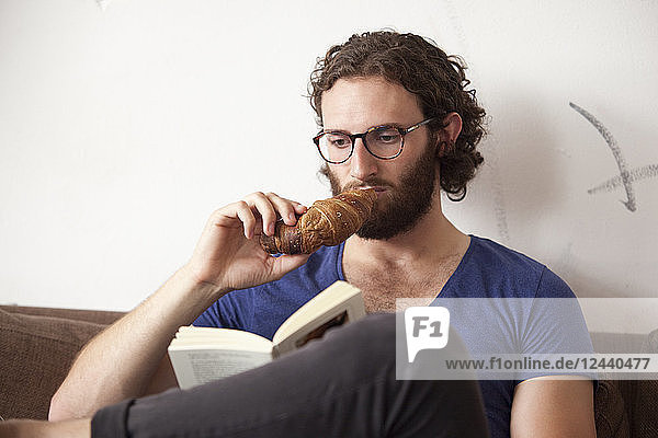 Portrait of young man eating croissant in a coffee shop while reading a book