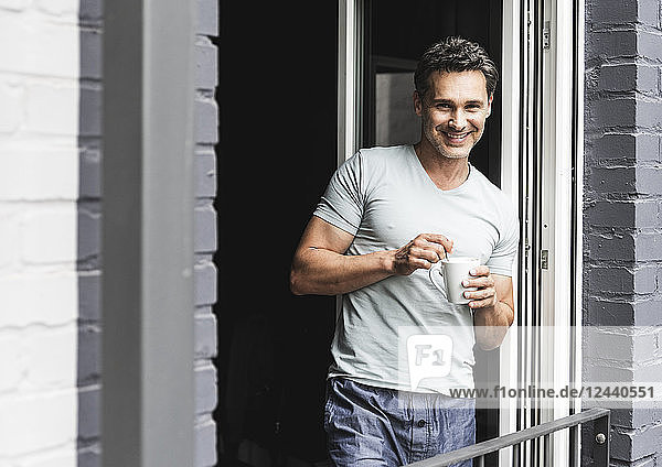 Portrait of smiling man in pyjama at home with cup of coffee at balcony door