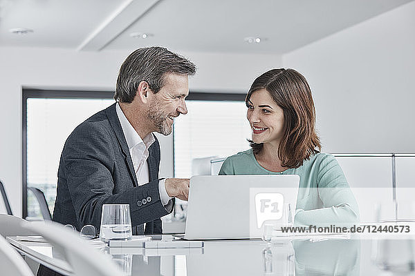 Businessman and businesswoman having a meeting in office with laptop