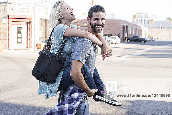 Happy young man carrying girlfriend piggyback