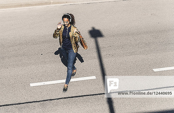 Young woman walking on empty road  wearing headphones  listening music