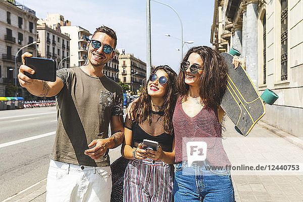 Three happy friends taking a selfie in the city