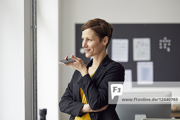 Attractive businesswoman standing in office  using smartphone
