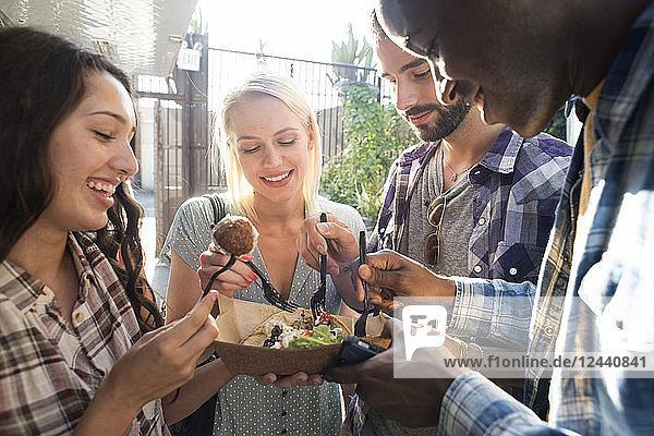 Happy friends sharing takeaway food outdoors