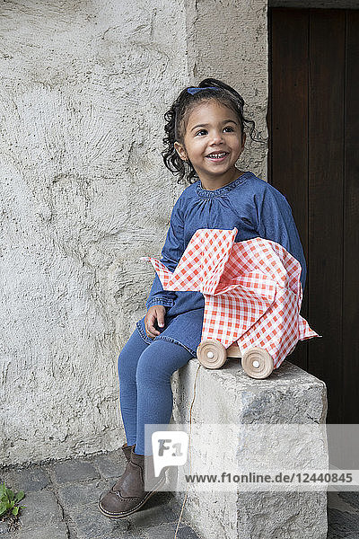 Little girl sitting on wall  origami elephant with rolls