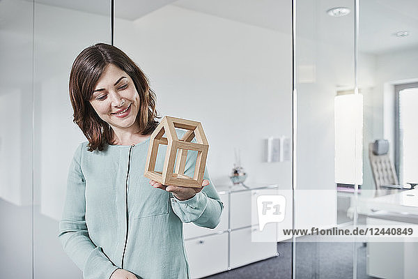 Smiling young businesswoman looking at architectural model in office