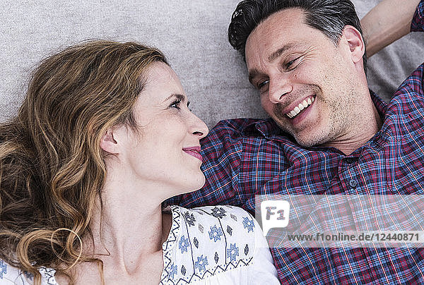 Happy affectionate couple lying on a blanket looking at each other