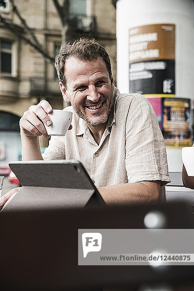Smiling man with tablet and coffee at an outdoor cafe