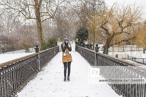 Teenage girl standing on footbridge in a park on a snowy day