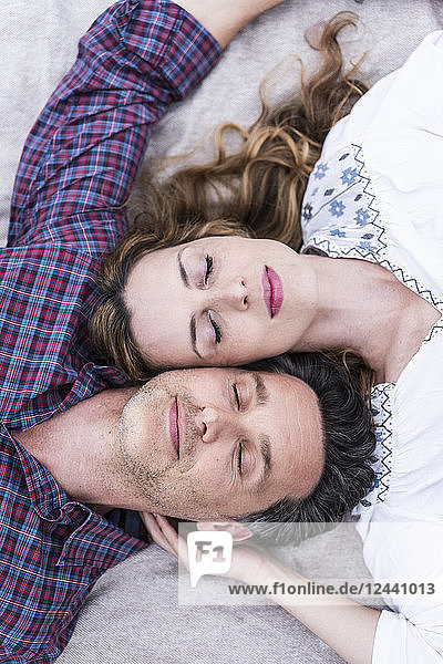 Affectionate couple with closed eyes lying on a blanket