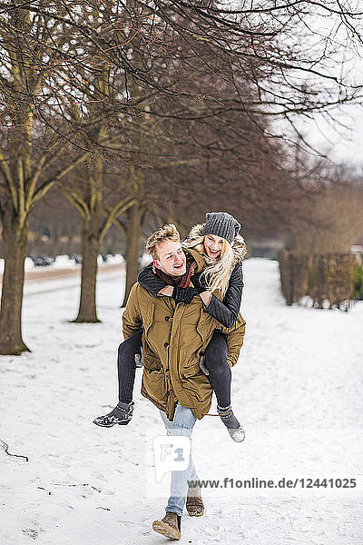 Young man giving his girlfriend a piggyback ride in winter