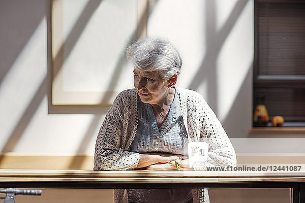 Lonely senior woman leaning on railing  looking down