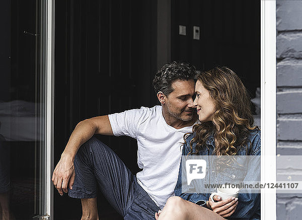 Affectionate couple in nightwear at home sitting at French window
