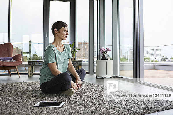Woman sitting on the floor at home with tablet looking out of balcony door