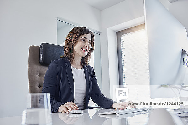 Smiling young businesswoman working at desk in office