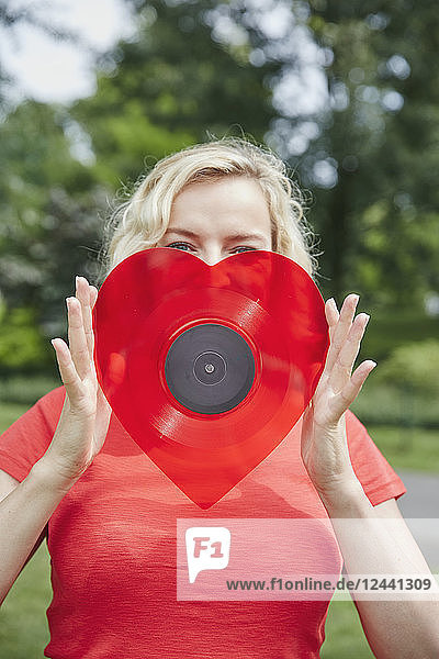 Woman holding a heart-shaped vinyl record outdoors