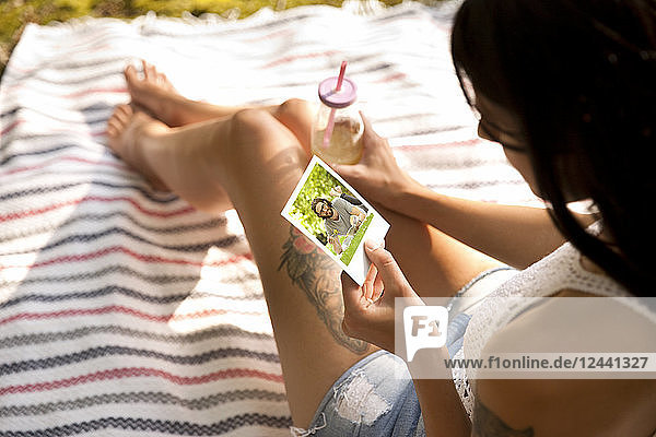 Young woman sitting on blanket looking at instant photo
