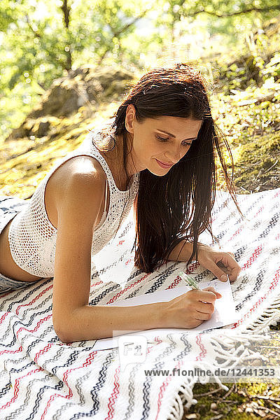 Young woman lying on blanket in forest writing a letter