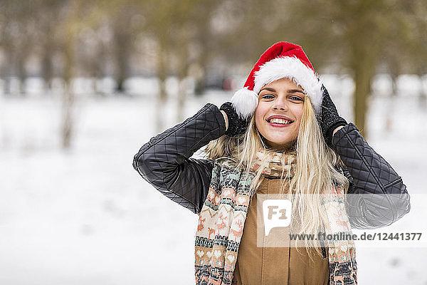 Portrait of smiling blond teenage girl wearing Christmas cap in winter