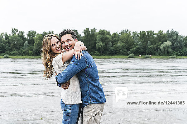 Portrait of happy couple hugging at the riverside