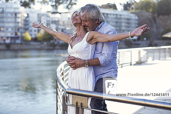 Senior couple taking a city break  embracing at a railing