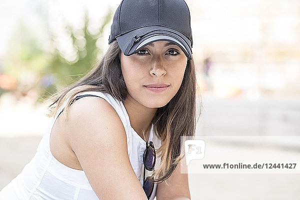 Portrait of young woman wearing baseball cap