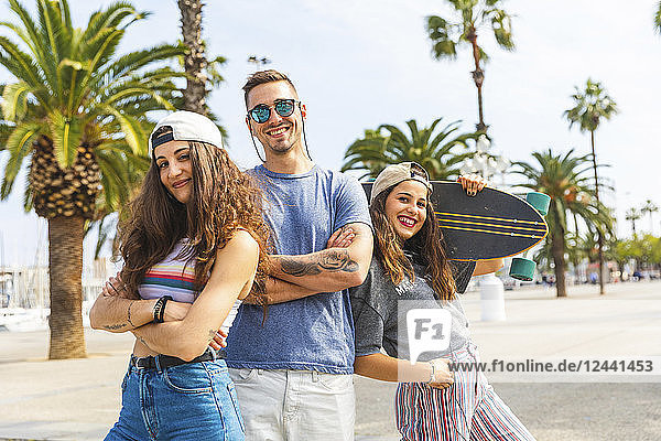 Three happy friends posing with skateboard on a promenade with palms