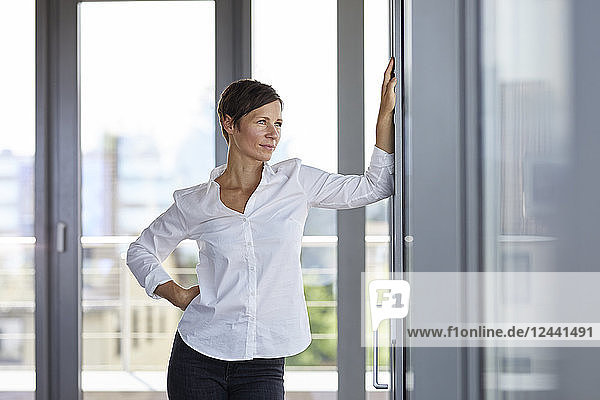 Businesswoman standing in office looking out of window