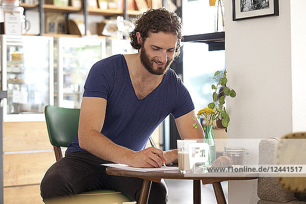 Smiling young man sitting in a coffee shop writing letter