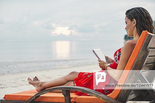 Thailand  Koh Phangan  woman sitting on sunlounger on the beach using digital tablet