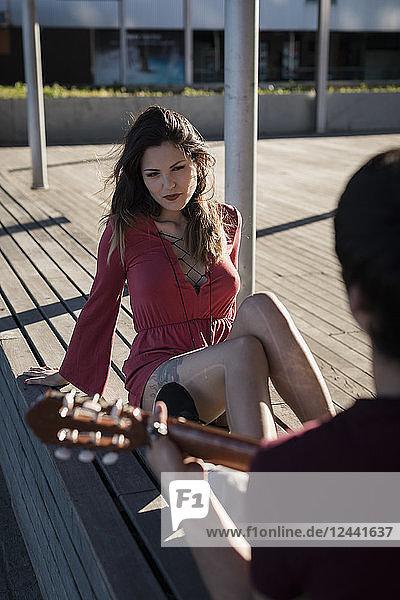 Young woman sitting on a bench watching boyfriend playing guitar
