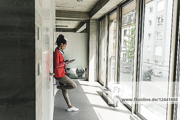 Young woman with headphones standing in corridor  using digital tablet