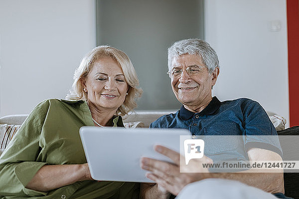 Senior couple at home sitting on couch sharing tablet