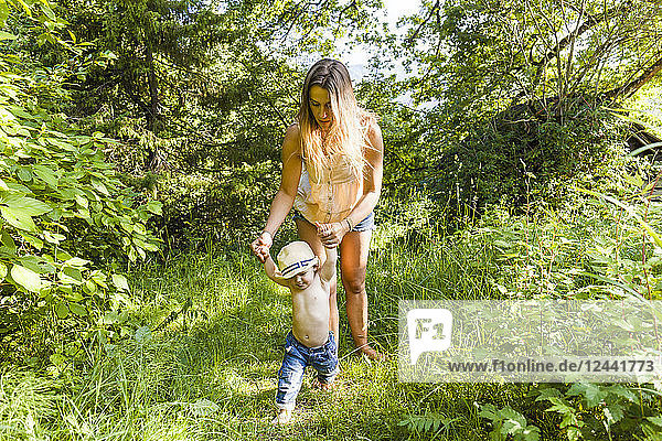 Mother helping baby boy to walk