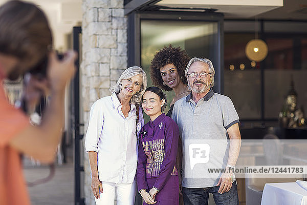 Family taking pictures with Asian waitress in front of restaurant