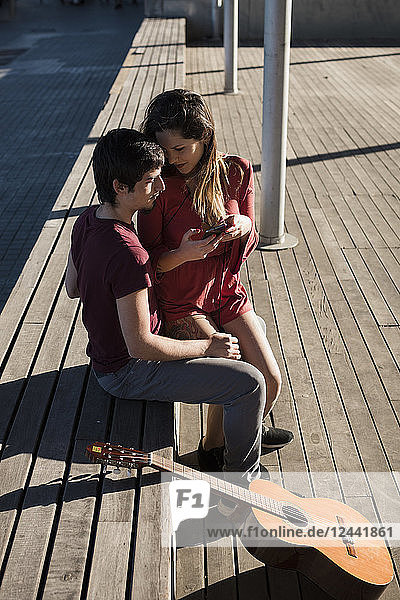 Affectionate young couple sitting on a bench with cell phone and guitar