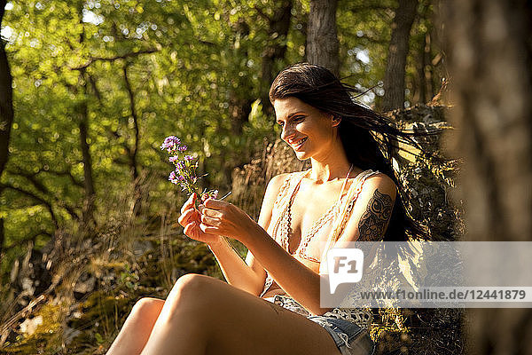 Young woman in forest binding bunch of flowers