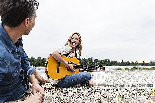 Happy woman with man at the riverside playing guitar