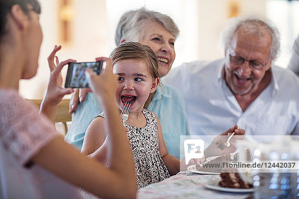 Grandparents celebrating a birthday with their granddaughter  taking picture with smartphone
