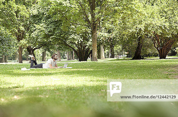 Man lying on blanket in a park using laptop