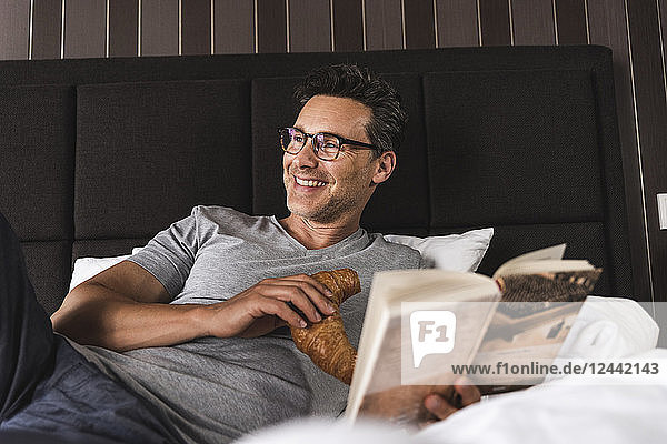 Happy man lying in bed at home with croissant and book